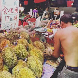 Local fruit market, the guy is selling durian.